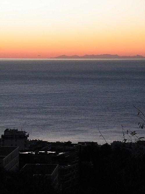 La Corse se découpe sur l'horizon au crépuscule depuis Nice