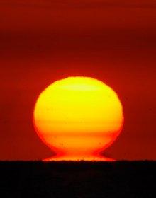 Un soleil jaune orangé posé sur l'horizon se dédouble sous l'effet de la réfraction atmosphérique